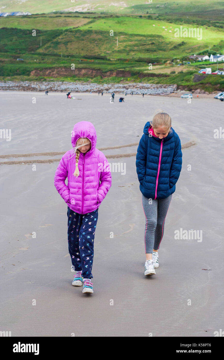 Children walking on a beach, heads down and hoods up, Kerry Ireland, irish concept, windy cold beach, hood up, hoods up, tide out - Stock Image