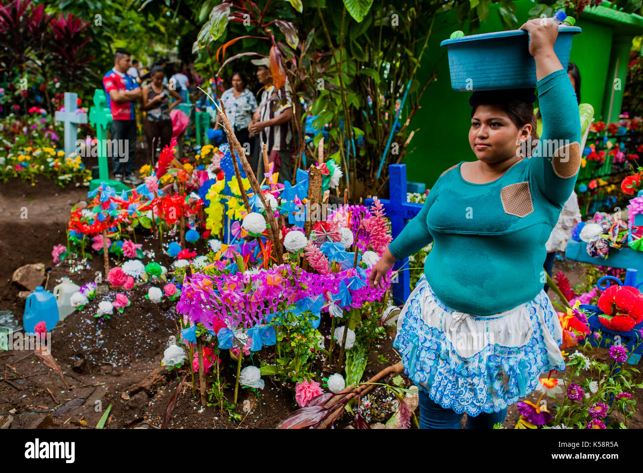 A Salvadoran vendor passes through the gravesites decorated with colorful flowers during the Day of the Dead celebration at the cemetery in Izalco, El - Stock Image