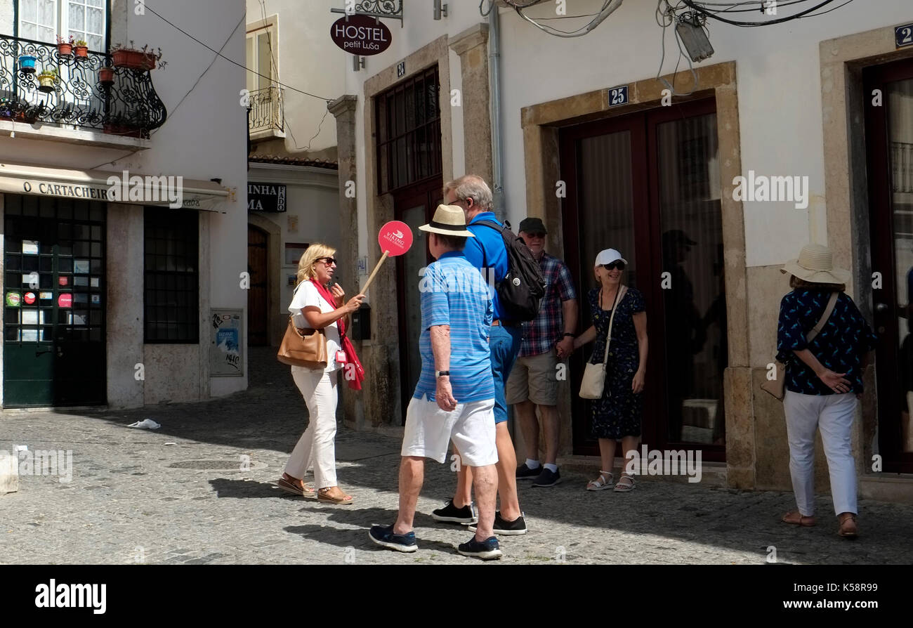 A tour guide leads a group of tourists in the old quarter of Lisbon, in Portugal August 26, 2017.  © John Voos - Stock Image