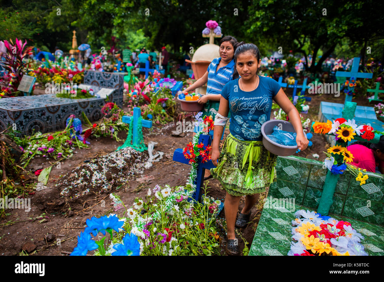 Salvadoran vendors pass through the gravesites decorated with colorful flowers during the Day of the Dead holiday Stock Photo