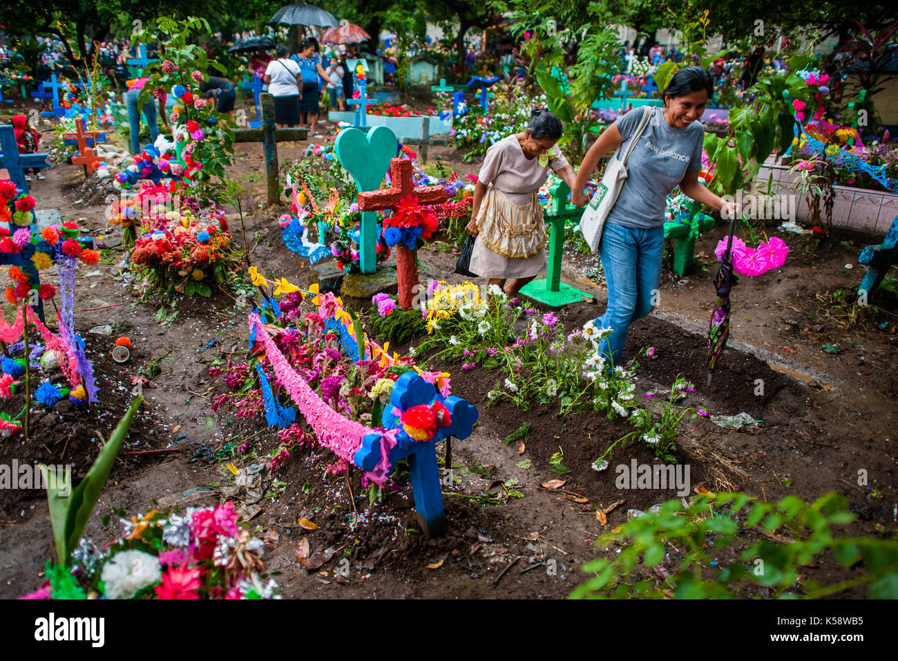 Salvadoran women pass between the gravesites decorated with flowers during the Day of the Dead holiday at the cemetery Stock Photo