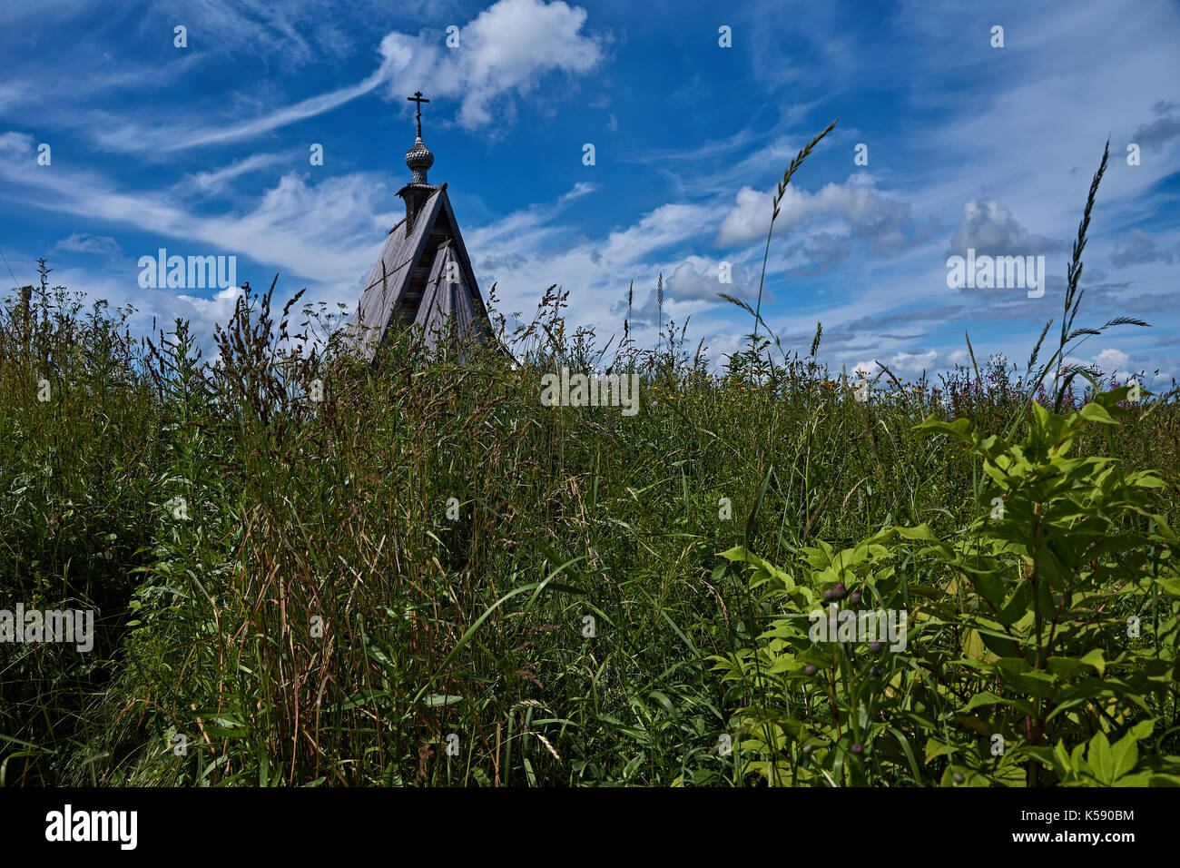 A wooden Orthodox church stands on a hill. Near the church there is an ancient rural cemetery with wooden crosses. Plyos, the Golden ring of Russia - Stock Image