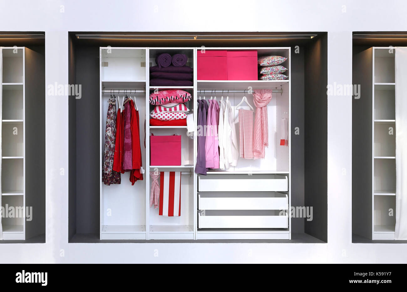 Inside Open Closet With Female Clothes And Accessories In Pink Colour Scheme