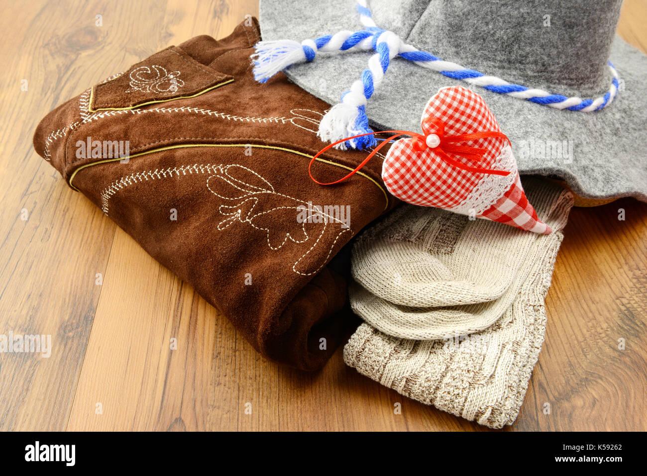 Oktoberfest cloths like lederhosen, felt hat and traditional socks on wooden table. store - Stock Image