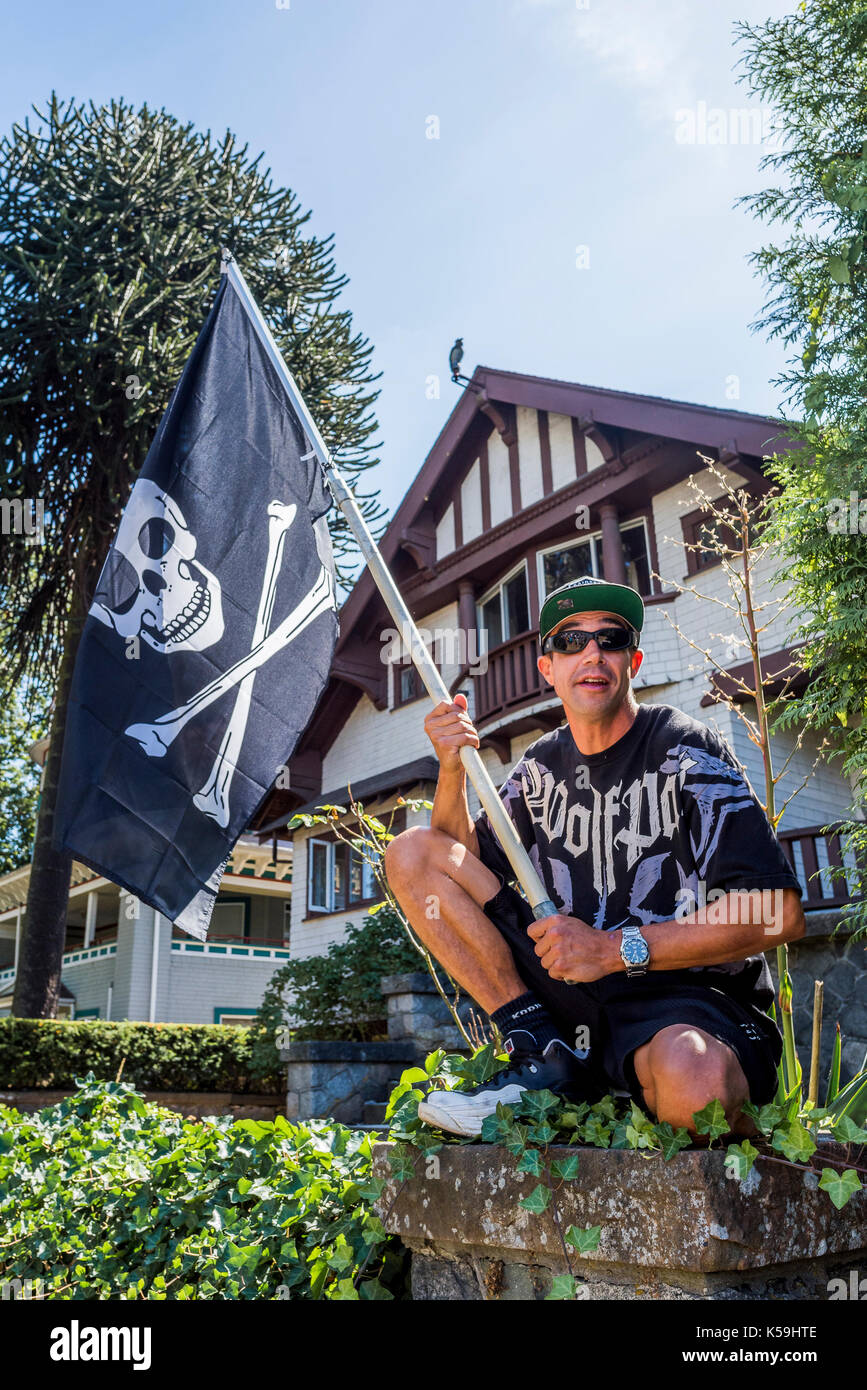 Man with Jolly Roger pirate flag at Anti-Racism Rally, City Hall, Vancouver, British Columbia, Canada. - Stock Image