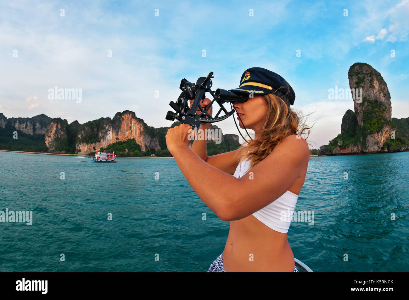 Young captain woman in cap on deck of sailing yacht taking sight in sextant to measure boat altitude position in tropical sea on summer cruise. - Stock Image