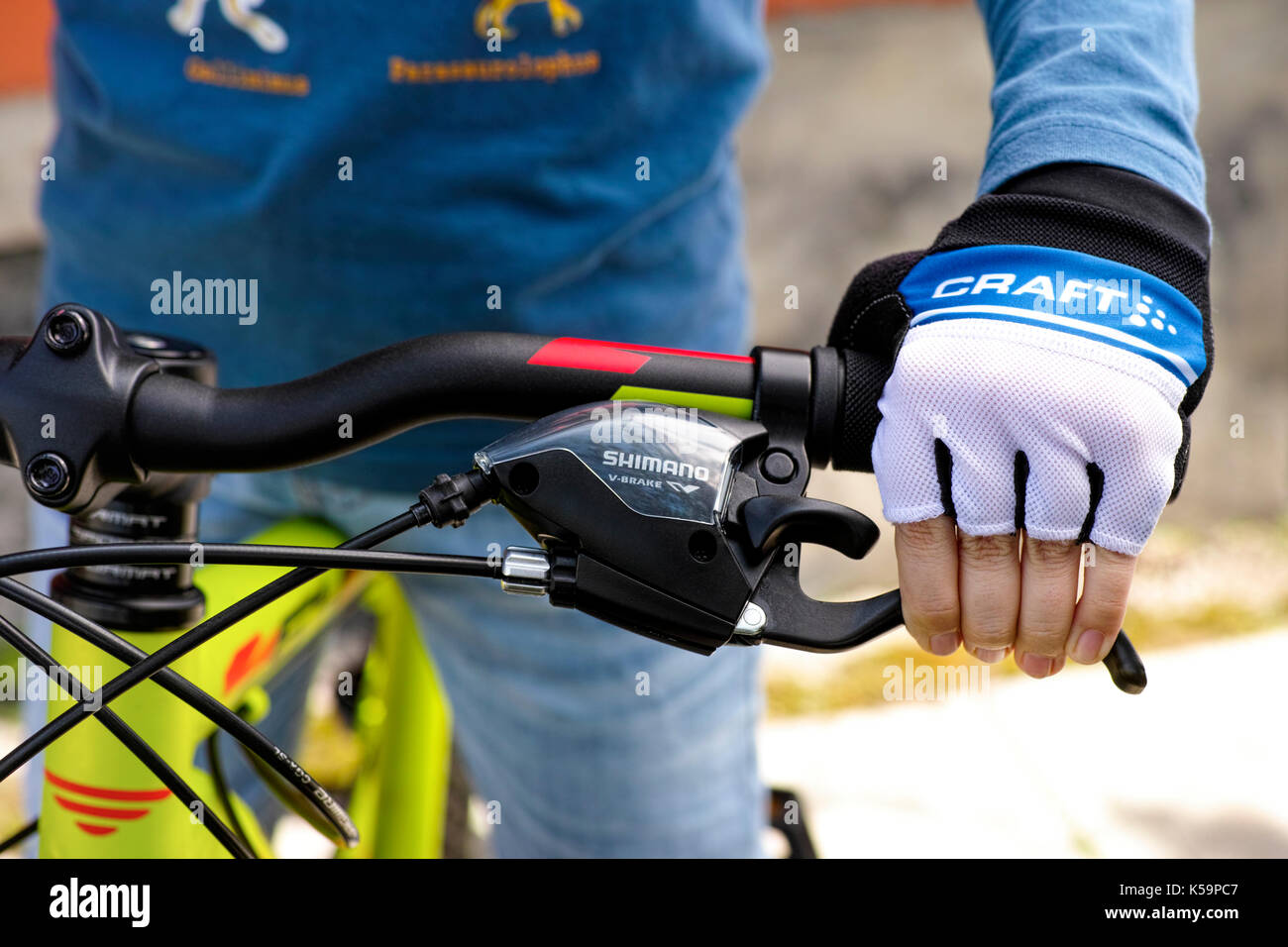Tambov, Russian Federation - May 07, 2017 Child hand with Craft glove on handlebars with Shimano speed shift and Stock Photo