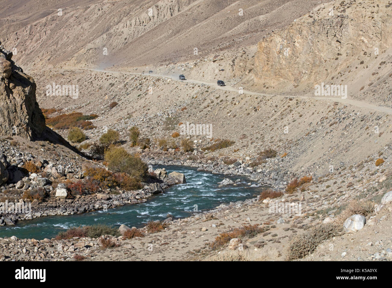 4WD vehicles driving on the Pamir Highway / M41 along the Pamir River in the Gorno-Badakhshan province, Tajikistan - Stock Image
