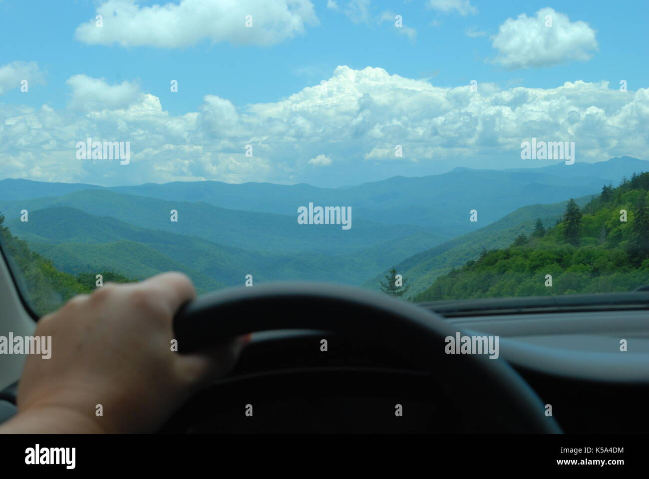 Driver stoped to watch Smoky Mountain. Man hand on steering wheel and fantastic view on blue mountains through the car window - Stock Image