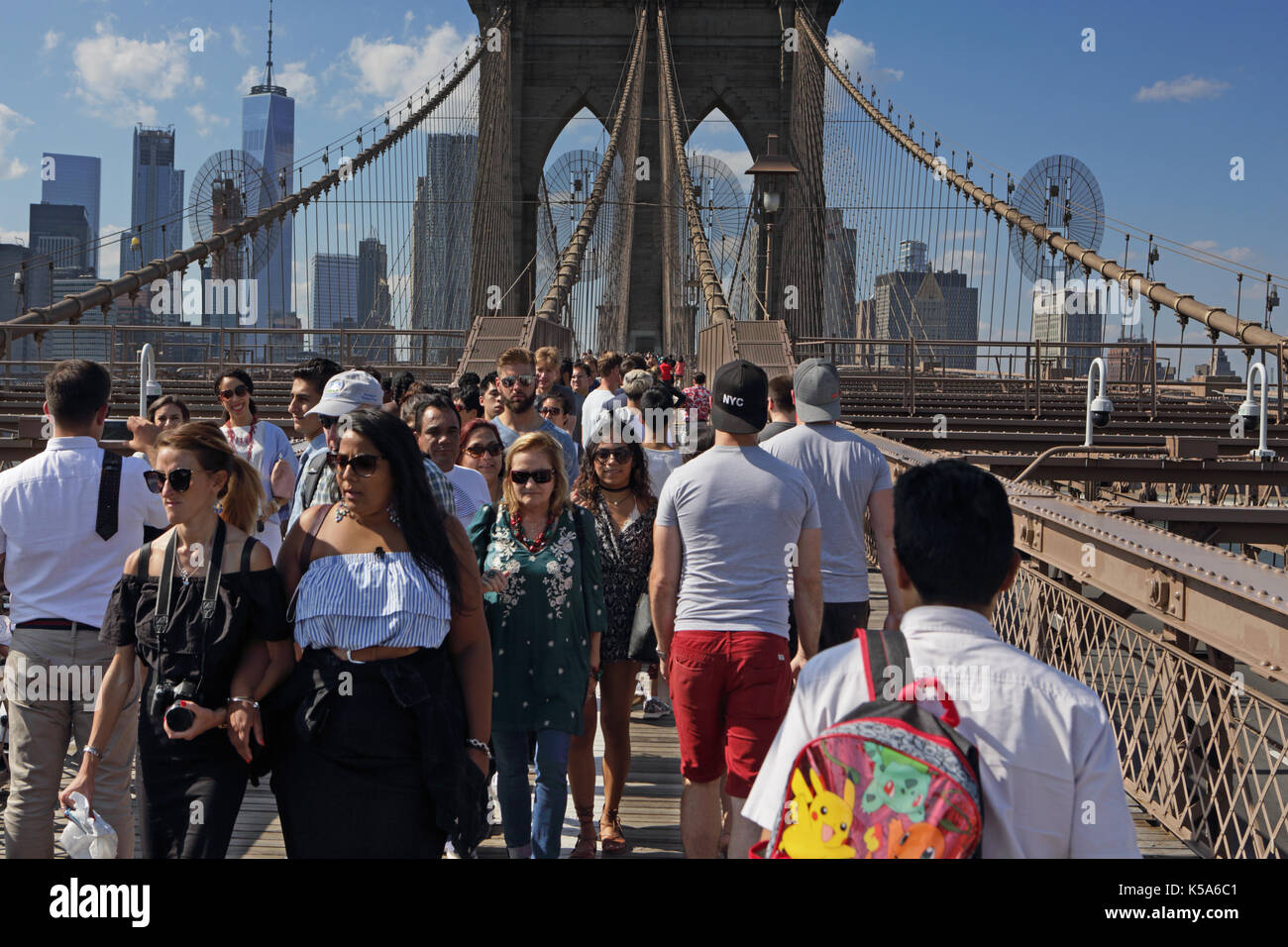 Crowds of tourists walk over Brooklyn Bridge on a sunny Labor Day holiday with Lower Manhattan in the background - Stock Image