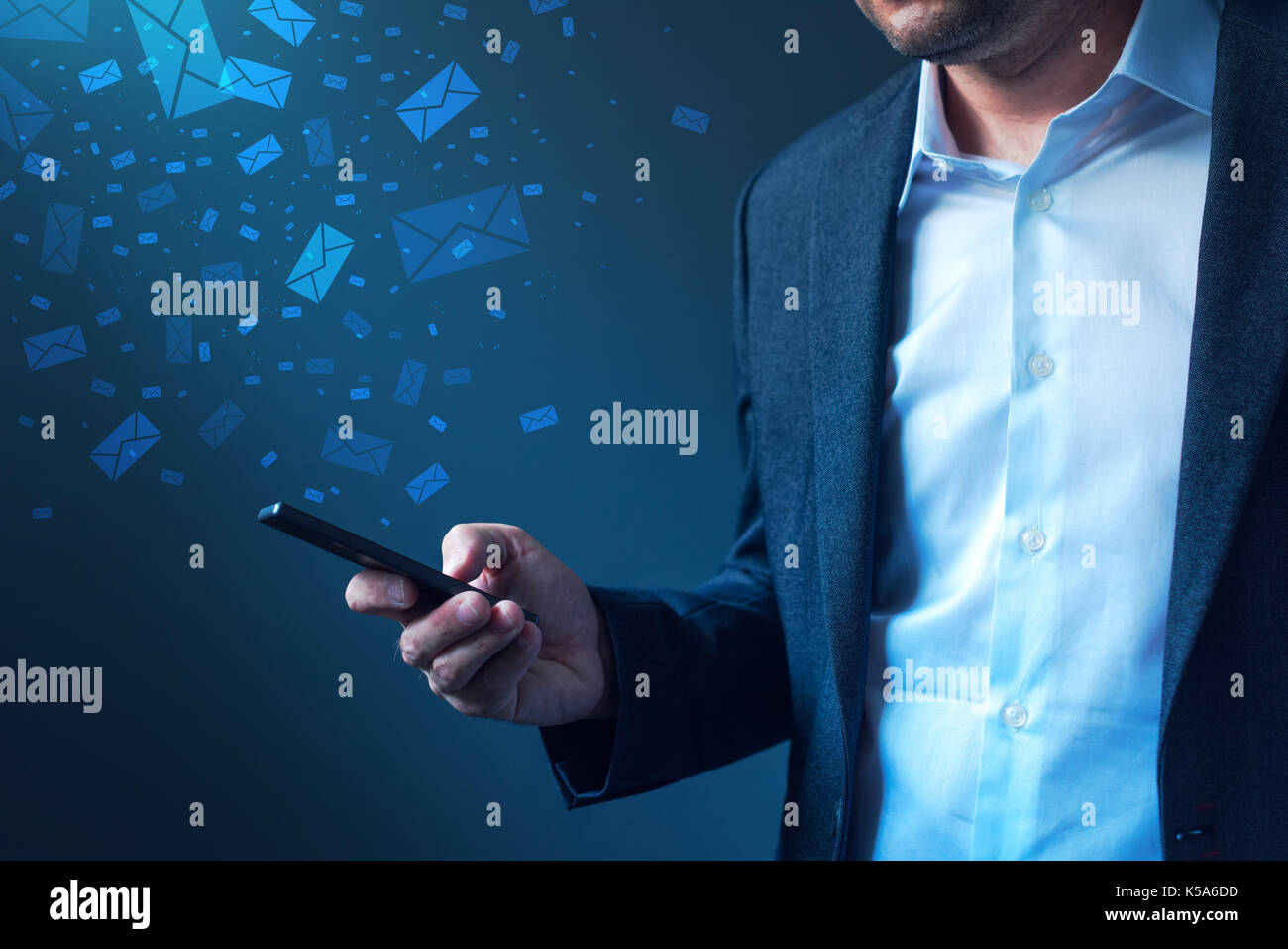 Businessman sending bulk messages using smartphone, male business person in elegant suit delivering e-mails, newsletters or SMS text messages with his - Stock Image