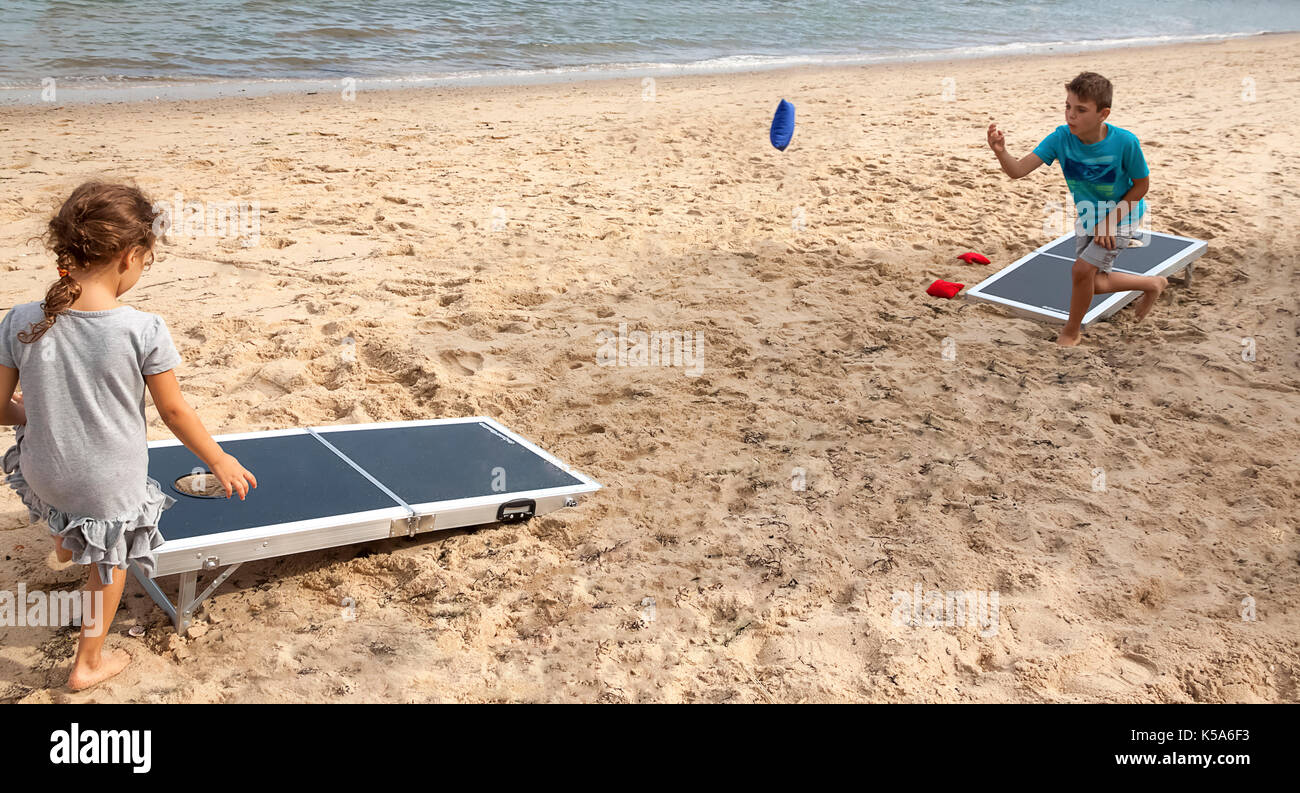 Children playing bean bag toss, cornhole, game on the beach. - Stock Image