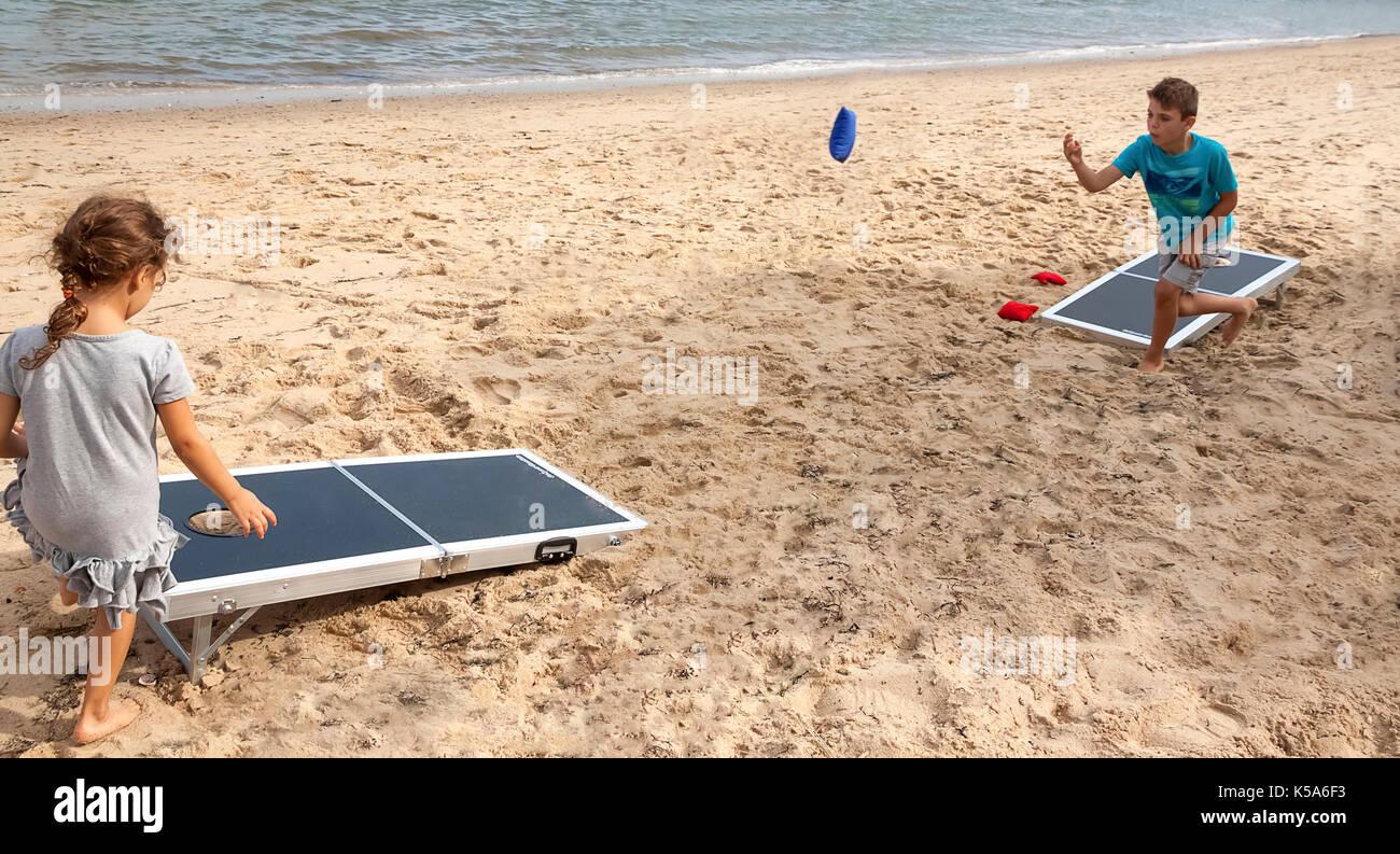 Children playing bean bag toss, cornhole, game on the beach. Stock Photo
