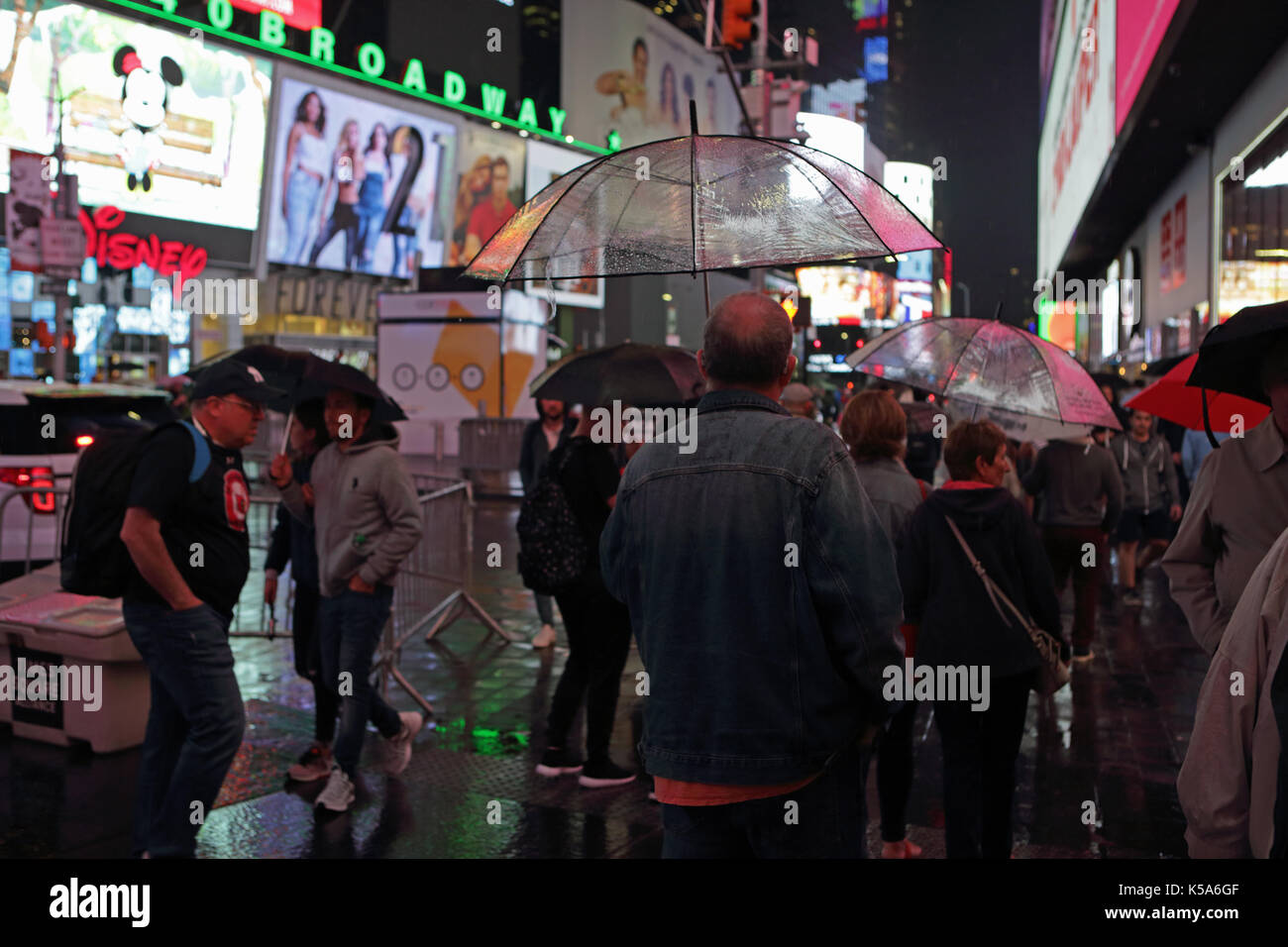 Rainy night in Times Square, tourists with umbrellas walk 7th Avenue and Broadway brightly lit by electric billboard advertising screens - Stock Image