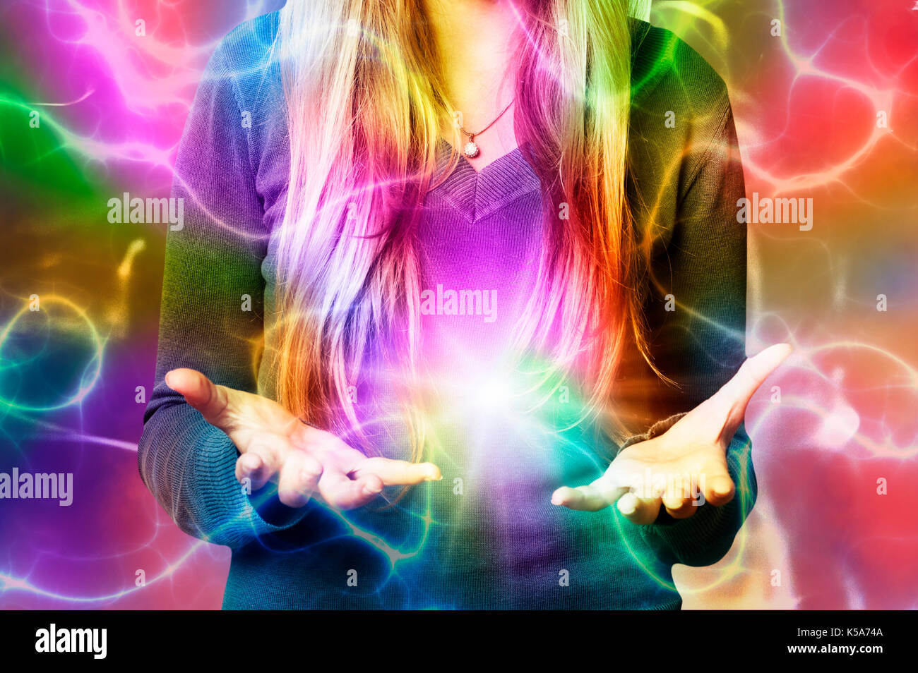 woman with hands open and colors all around, creativity and imagination concept - Stock Image