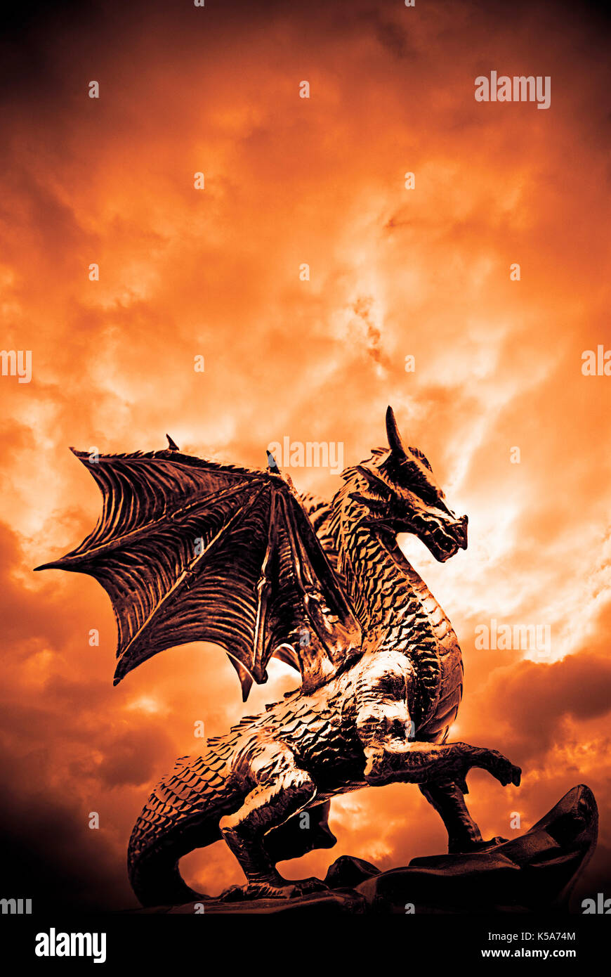 dragon statue with red dramatic sky - Stock Image