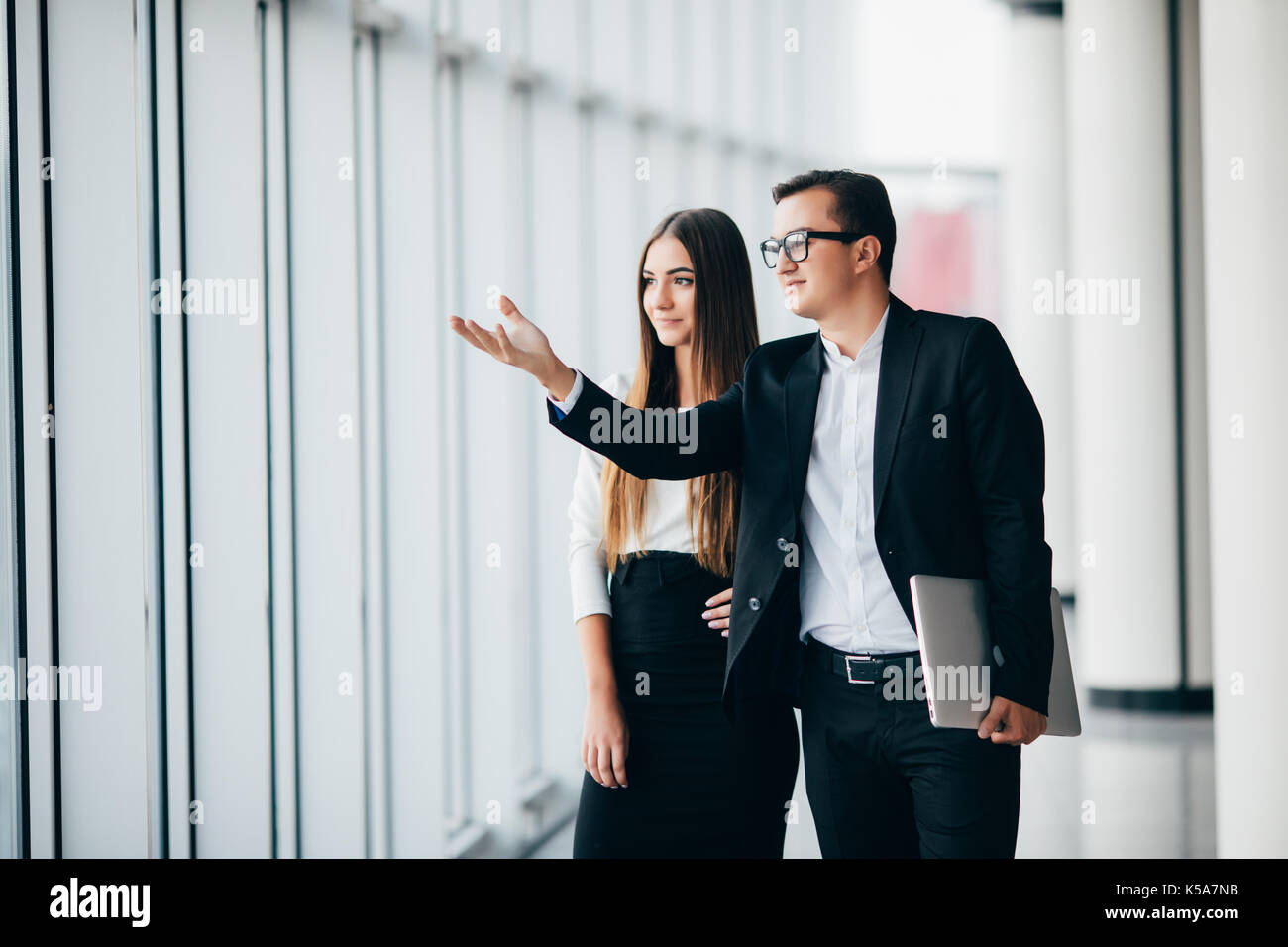 business man and business woman working with new start up project in modern office in Panoramic windows - Stock Image