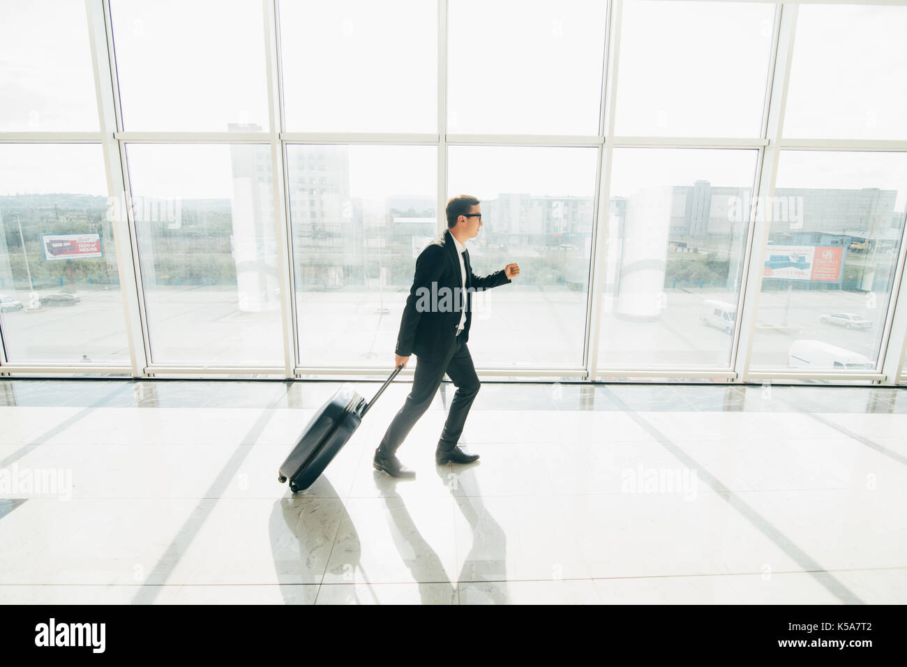 Business man at international airport moving to terminal gate for airplane travel trip - Mobility concept and aerospace industry flight connections - Stock Image