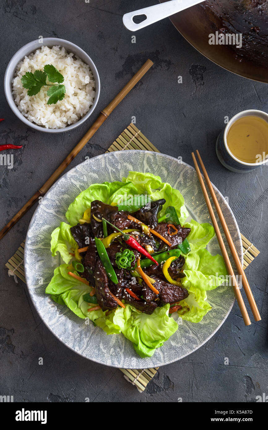 Asian stir fried chicken liver with bowl of rice and green tea - Stock Image
