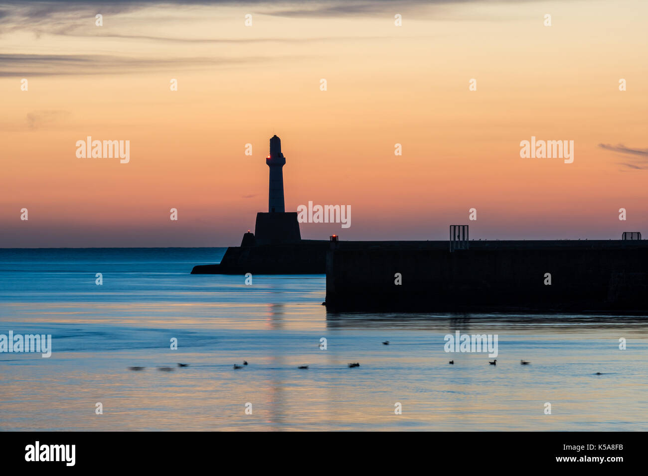 The lighthouse at the end of the main sea wall at the entrance to Aberdeen harbour. - Stock Image