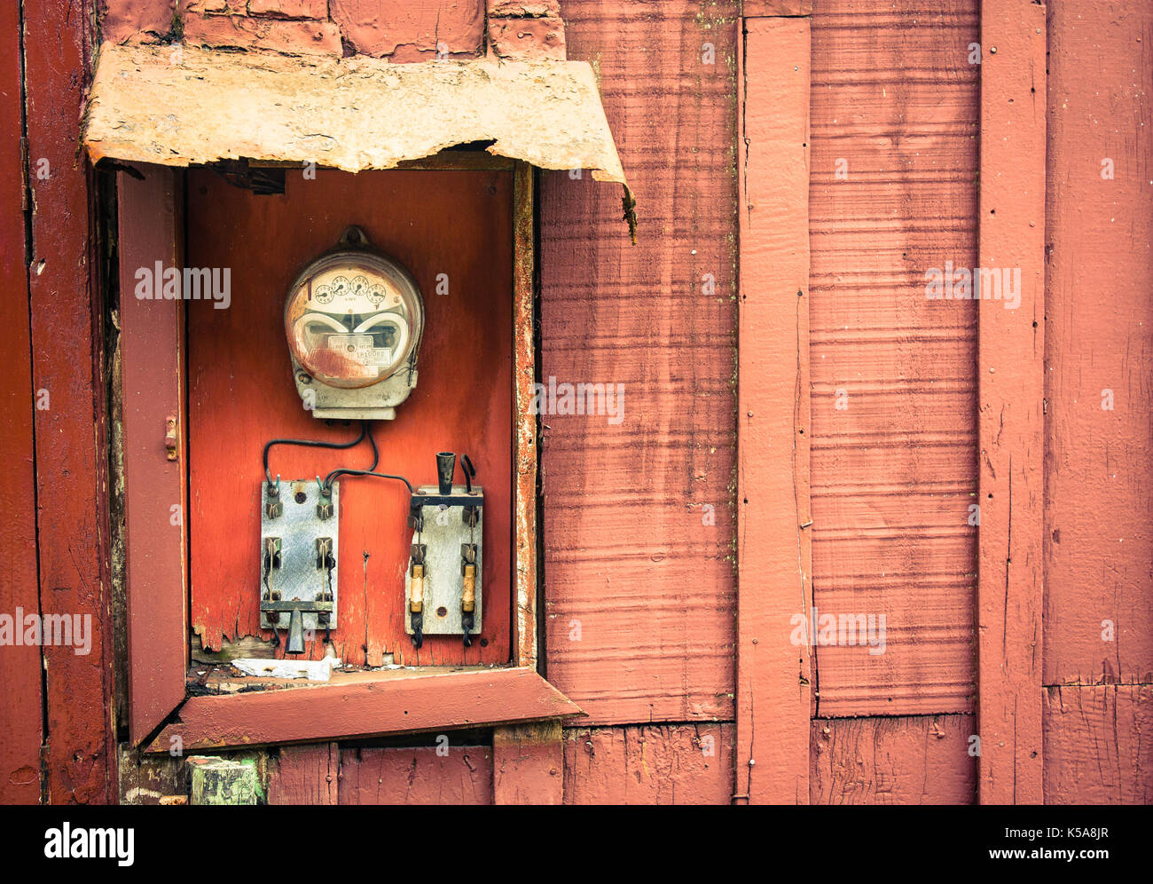 Old vintage and rusted analog electricity meter counter used for measurements in kWh of electricity usage with two switches on a red cracked and peeli - Stock Image