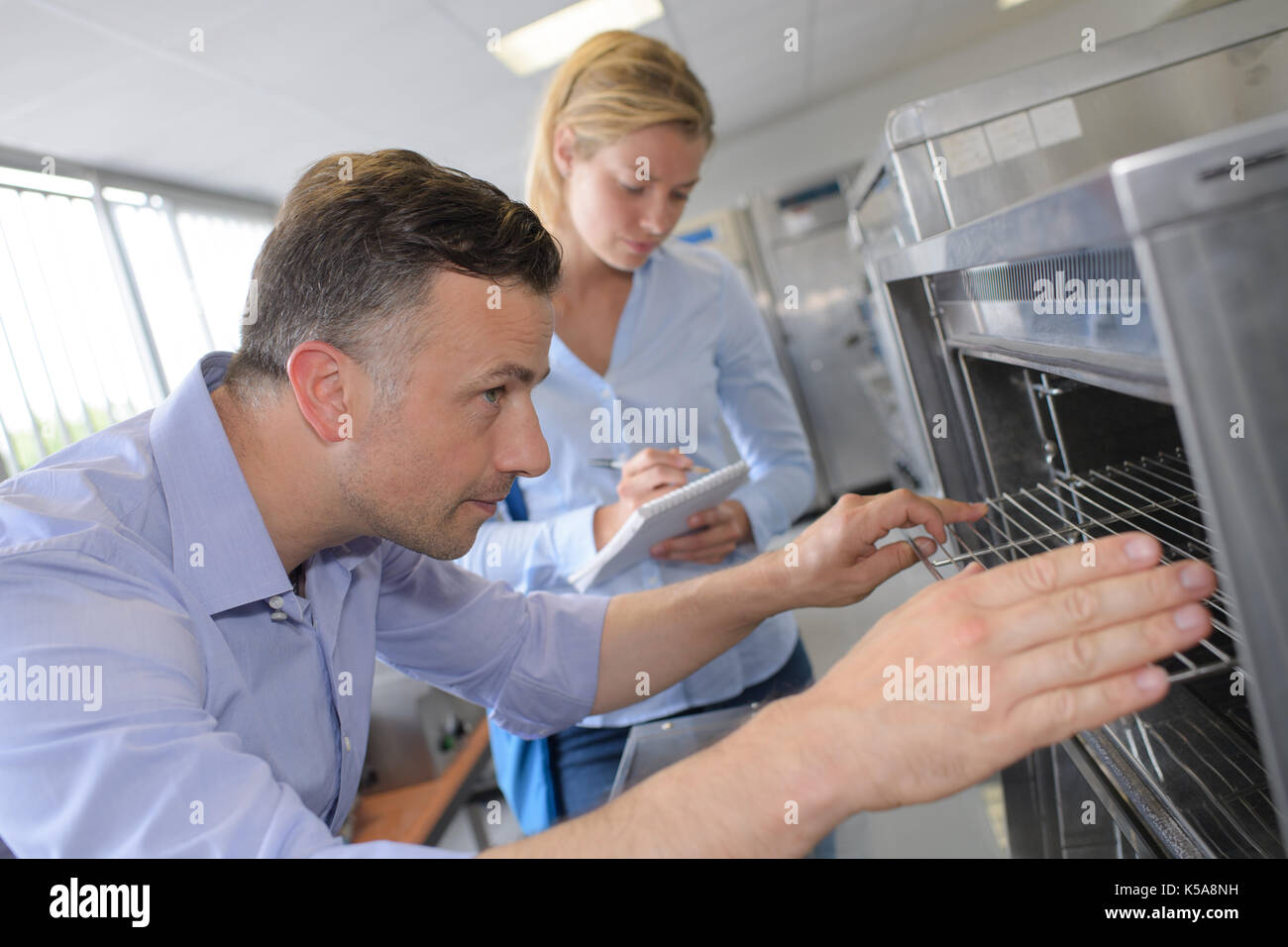 scientist opening high tech oven - Stock Image