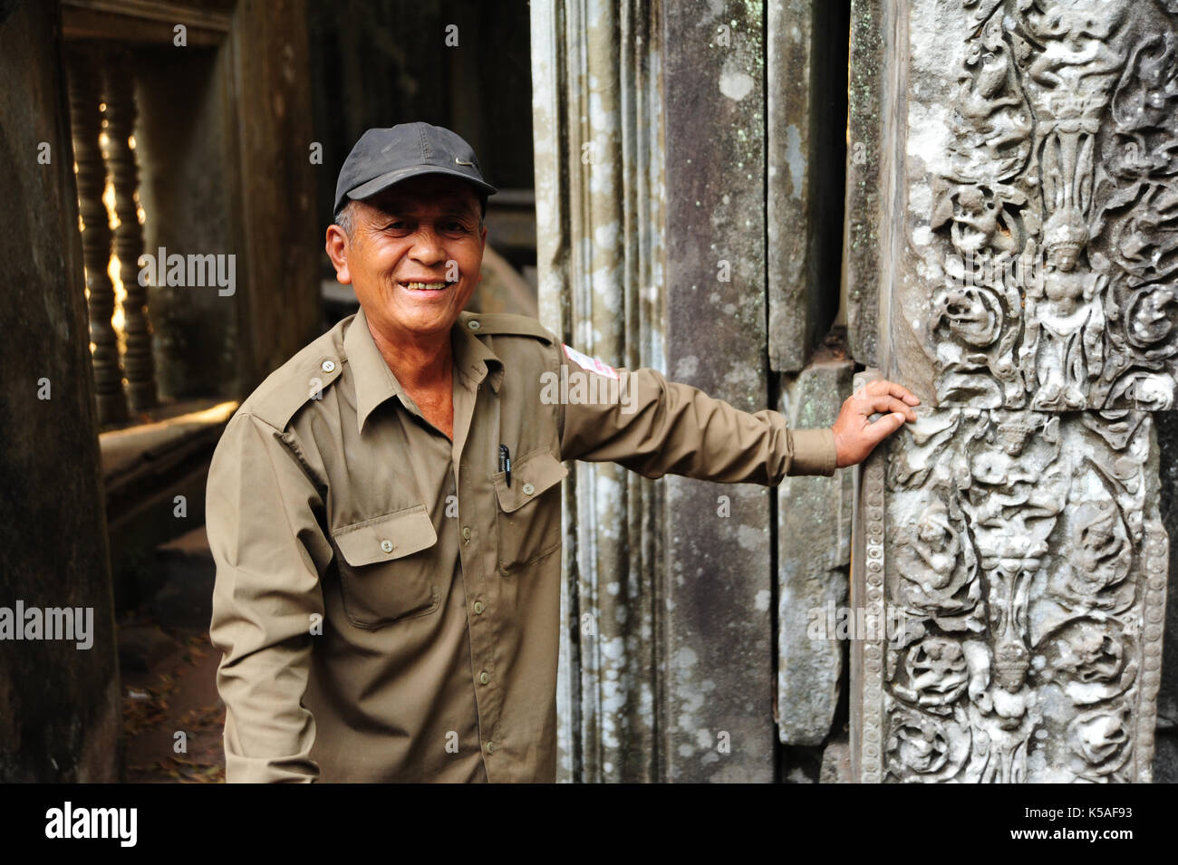 Siem Reap,Cambodia - Feb 11,2013:A local tourist guide standing next to a monument, background is a temple monument in Beng Mealea,Siem Reap,Cambodia. - Stock Image