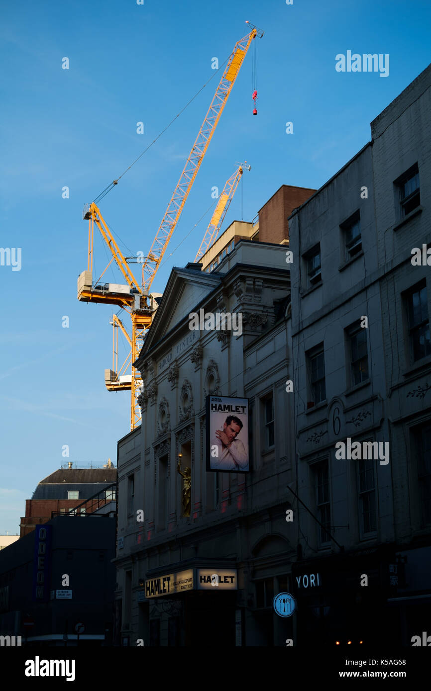 London theatre advertising Hamlet play with backdrop of towering yellow crane in sunlight with blue sky - Stock Image