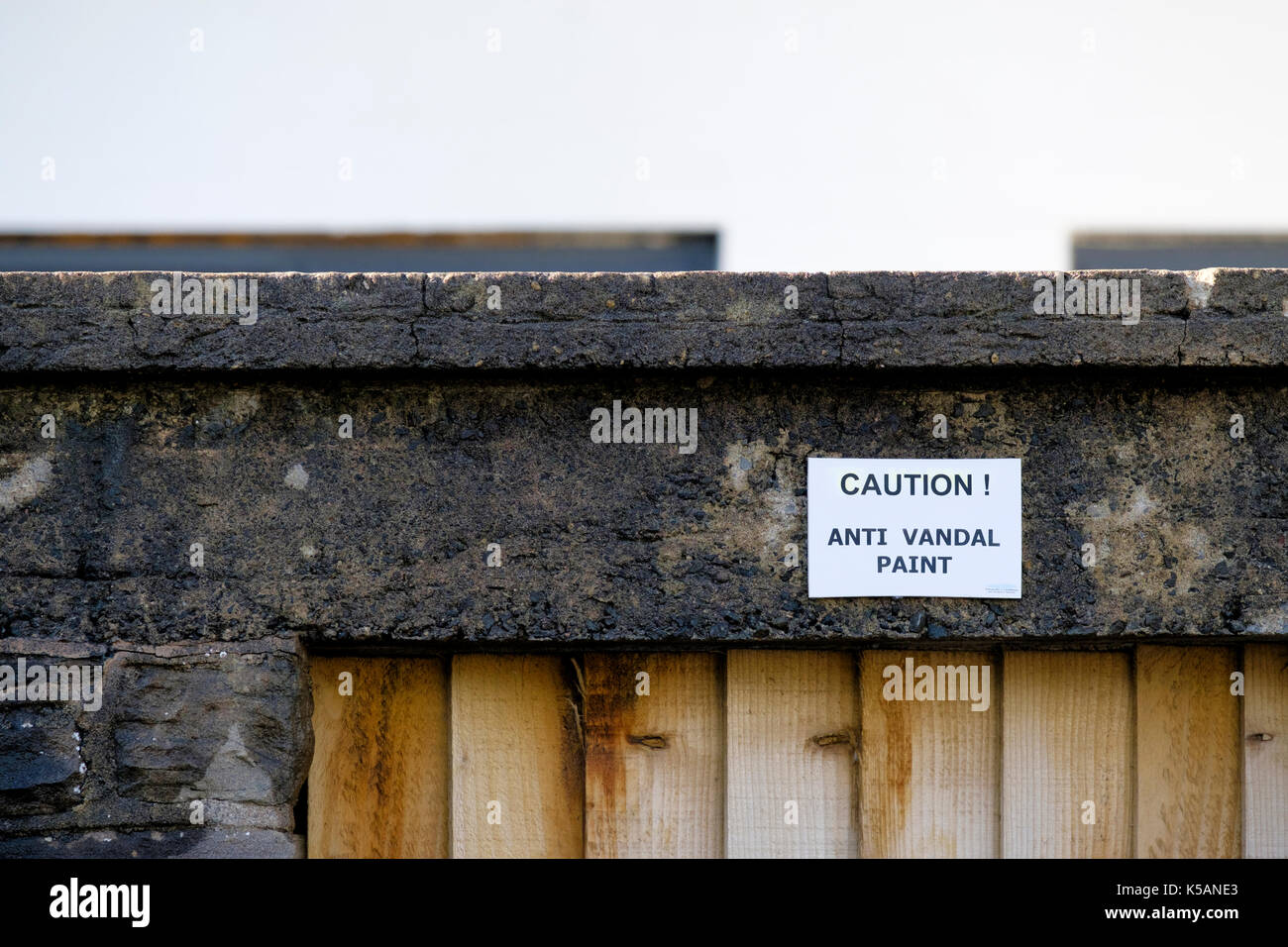 A mandatory sign placed on a house wall warning the the owner has used anti vandal paint in the vicinity - Stock Image