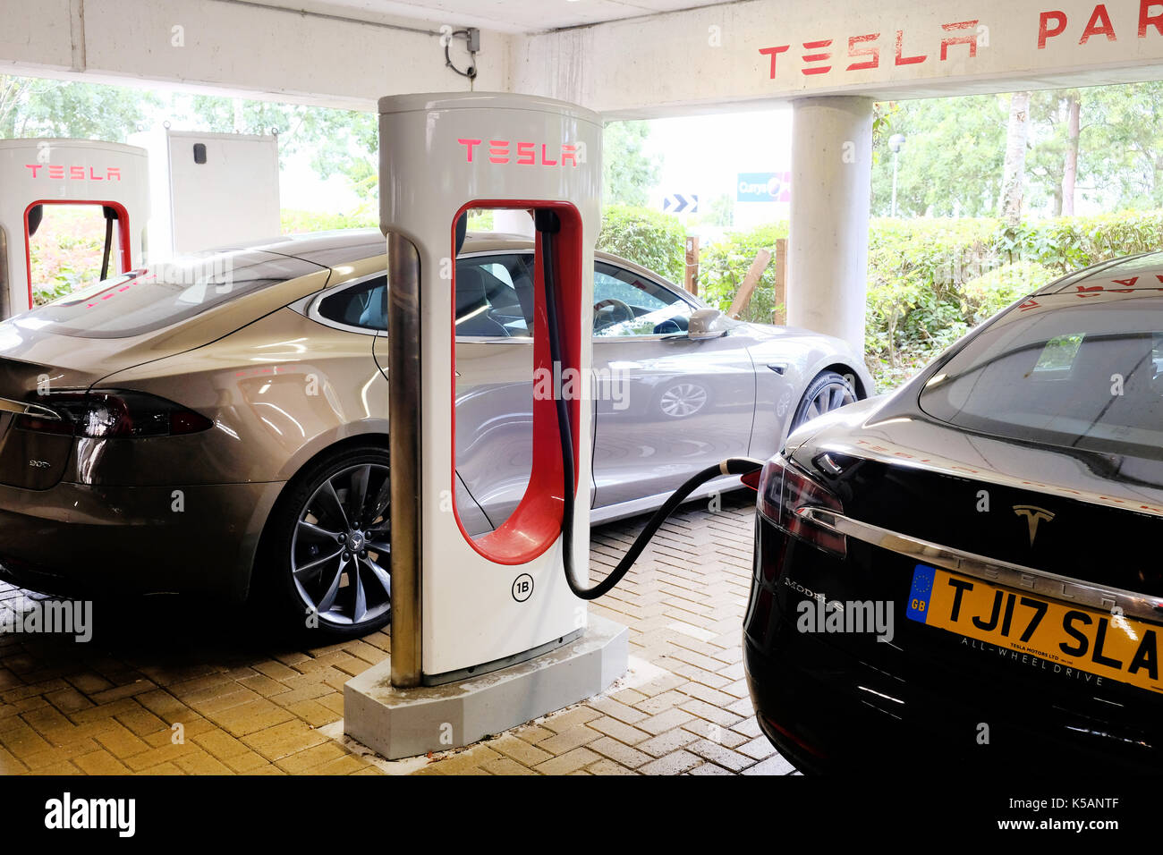 A tesla electric car being recharged at a clearly marked tesla charging station - Stock Image
