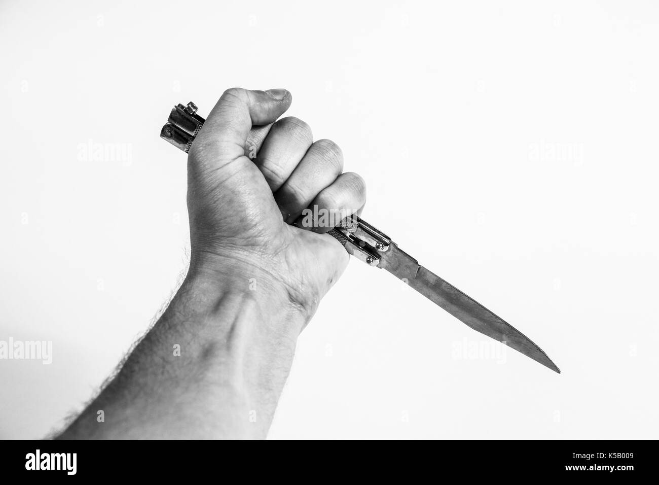 killer with a knife in his hand on a white background, is about to kill a victim Stock Photo
