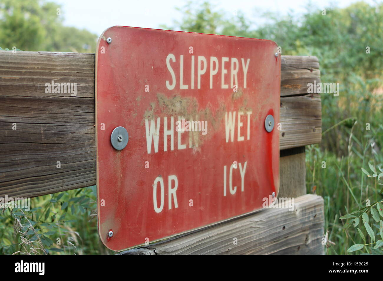Slippery when wet or icy sign on bridge along walking trail in Fountain Creek Regional Park, Fountain, Colorado - Stock Image