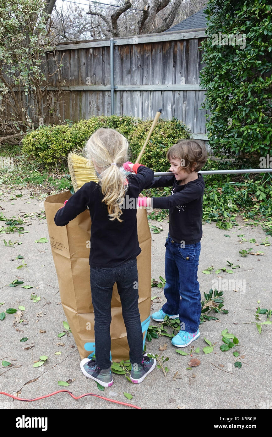 Two little girls helping with yard work - Stock Image