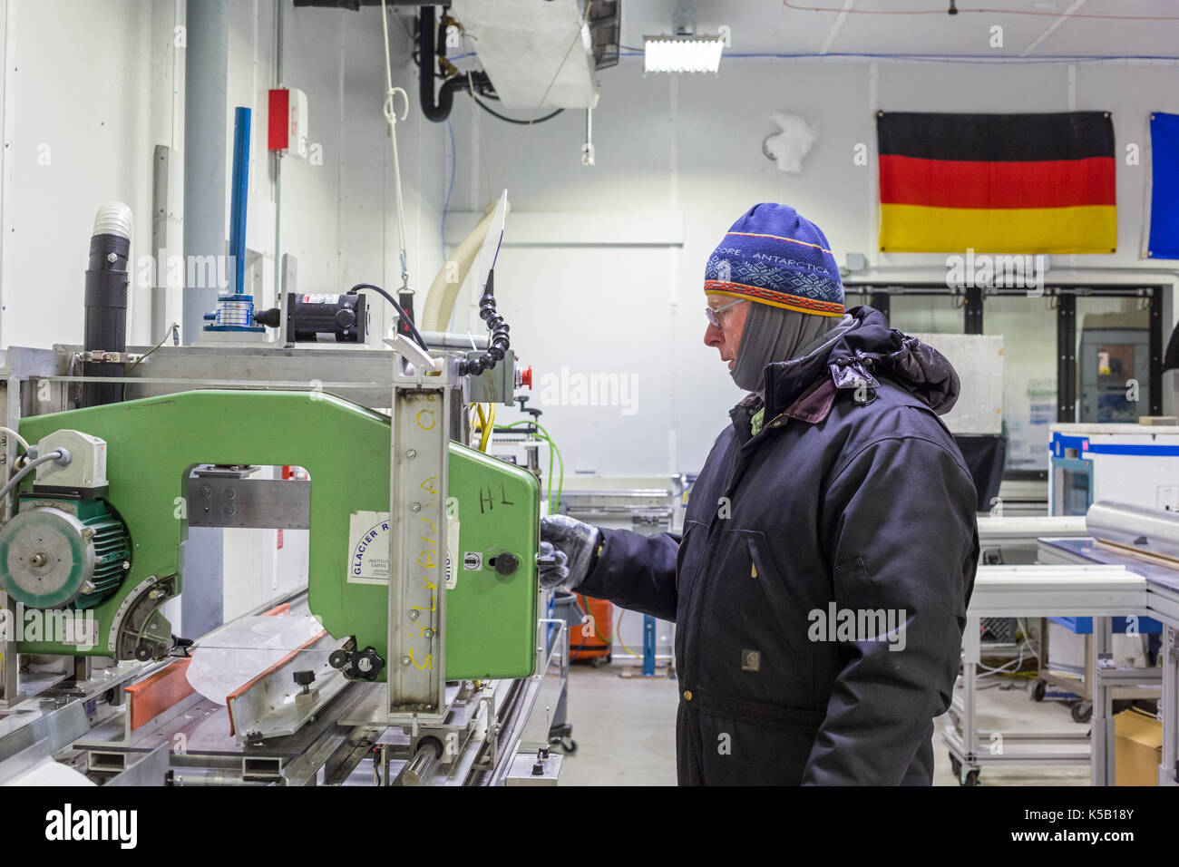 Denver, Colorado - Geoff Hargreaves, curator at the National Ice Core Laboratory, cuts an ice core from Greenland. The lab stores 19,000 meters of ice - Stock Image