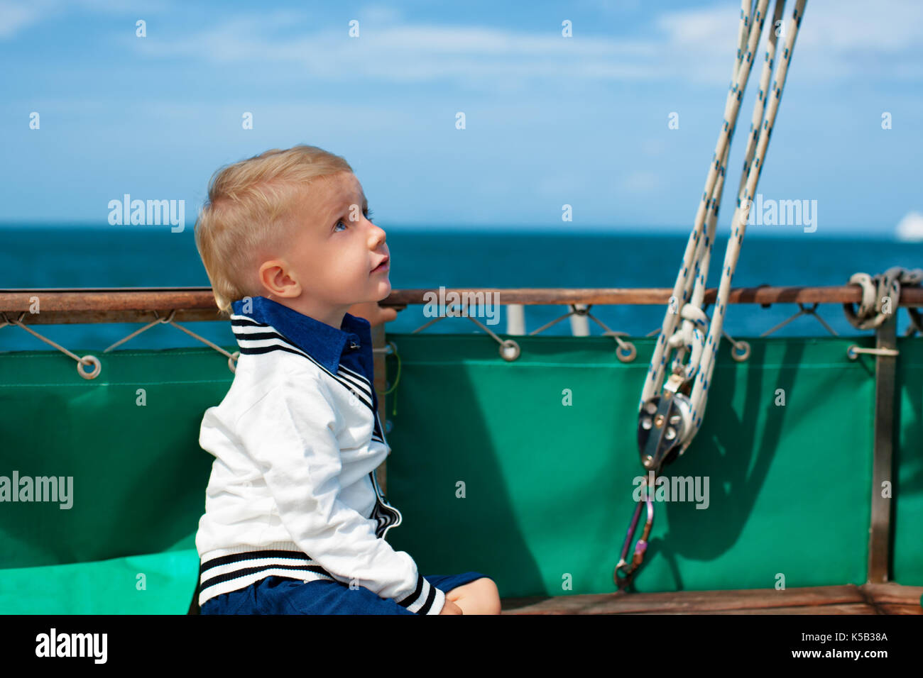 Joyful young captain portrait. Happy child on deck of sailing yacht, have fun discovering islands, travel in tropical sea on summer cruise. - Stock Image