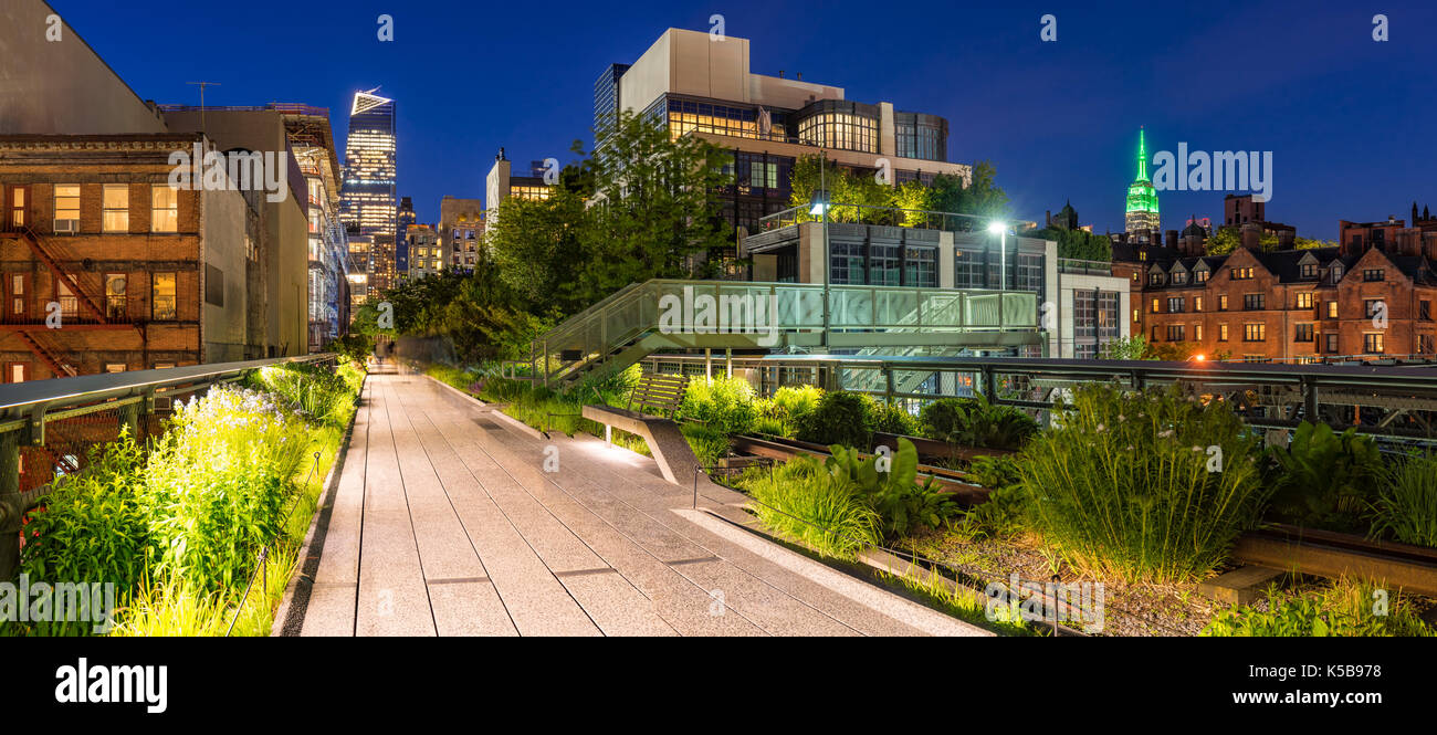 Panoramic view of the High Line promenade at twilight with city lights and illuminated skyscrapers. Chelsea, Manhattan, New York City - Stock Image