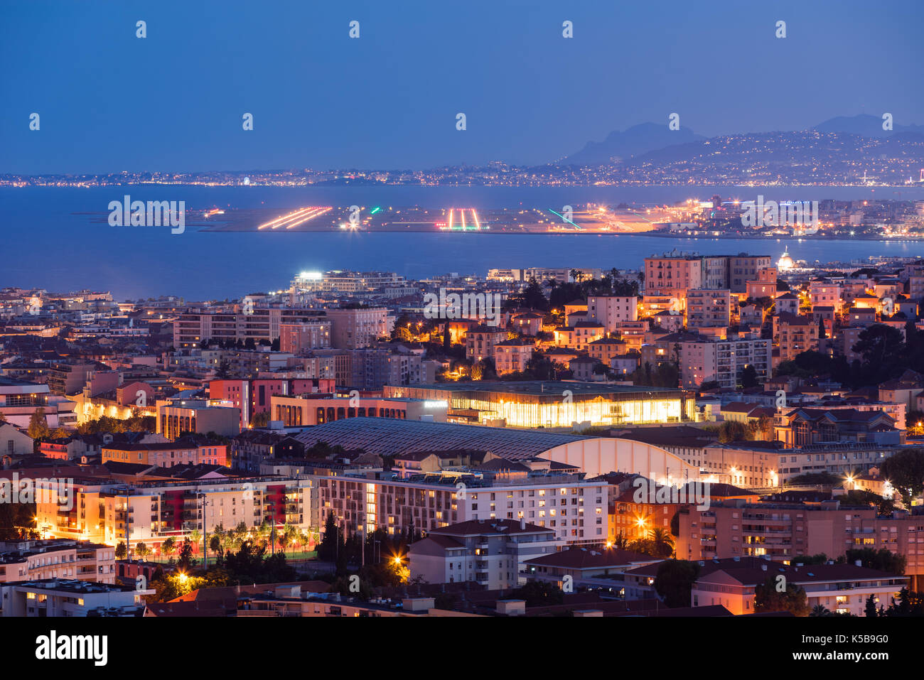 Elevated view of rooftops of Nice at twilight with the airport runways in the distance. French Riviera, Provence-Alpes-Cote d'Azur, France - Stock Image