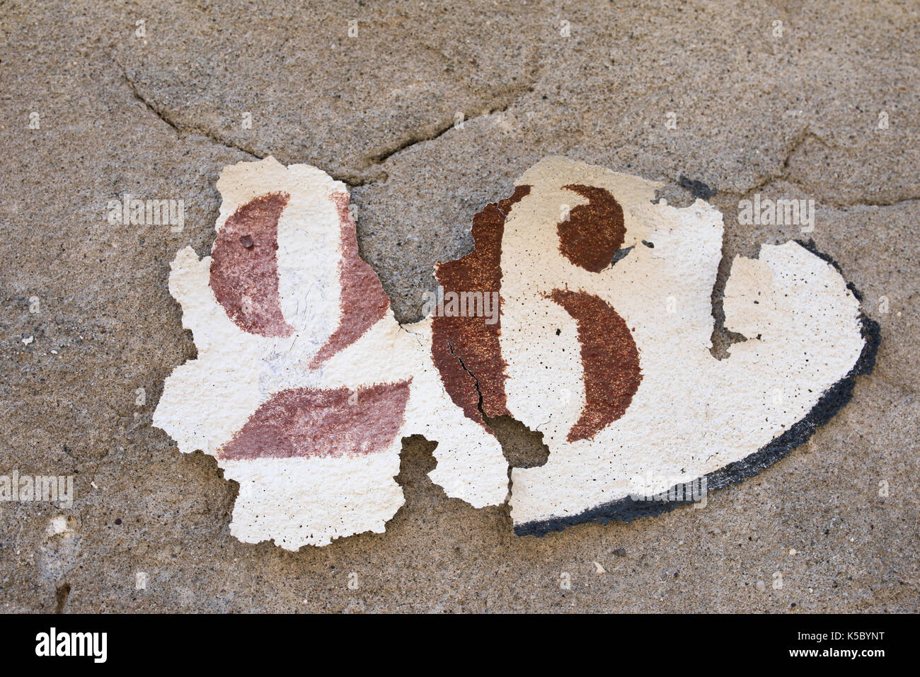 The peeling paint layer.  Painted number 26, destroyed  by weather, walls of the city Venice. Italy. The humidity, damp, dampness, water influence. - Stock Image