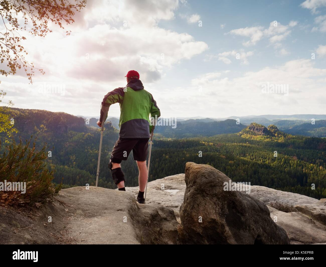 Man with forearm crutches. Hiker after hard walk achieved mountain peak. Tourist with broken leg in immobilizer hold medicine  poles. - Stock Image