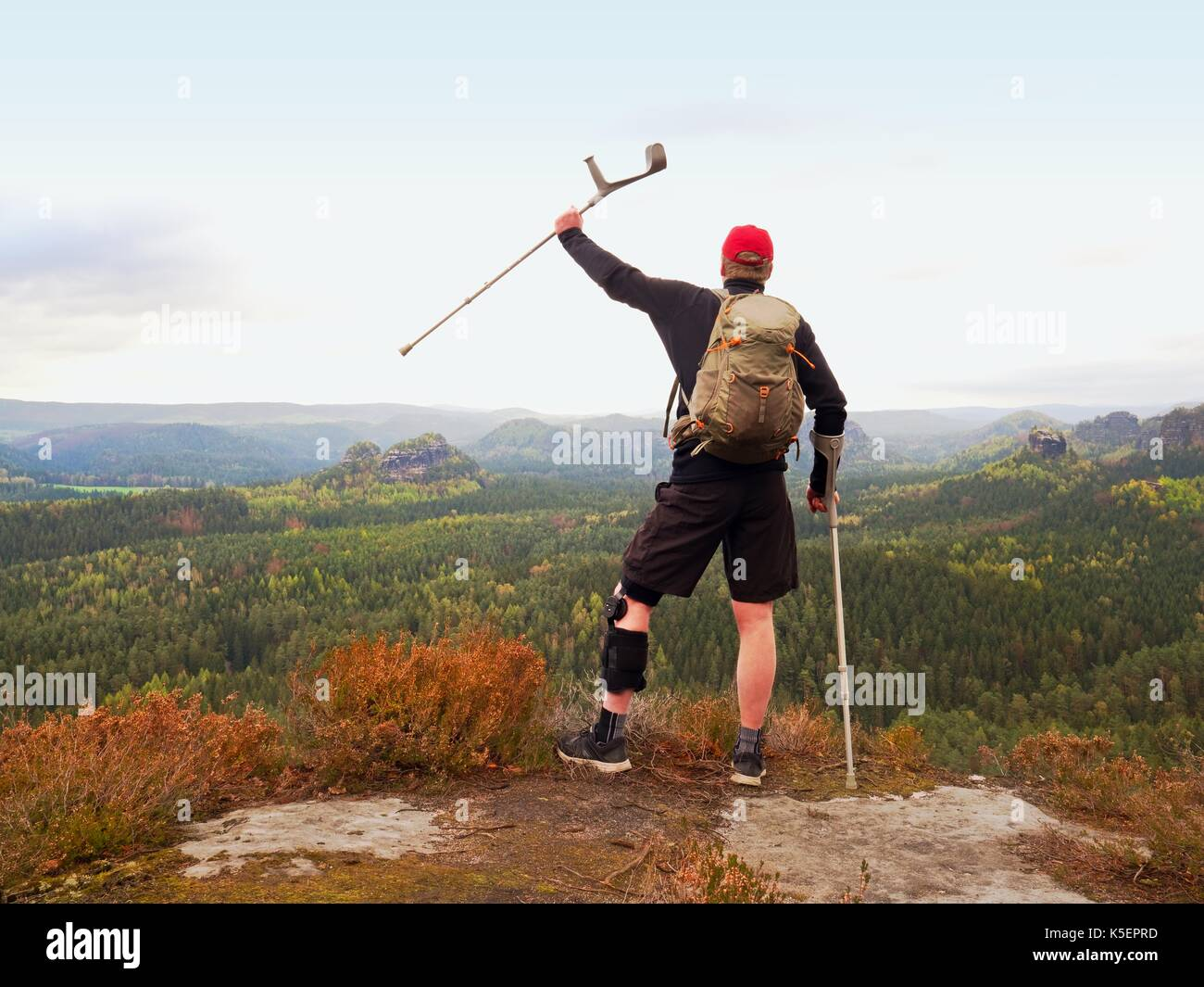 Wounded tourist with crutch above head achieved mountain peak. Hiker with backpack and  knee brace feature. Deep valley bellow man with hand in air. S - Stock Image