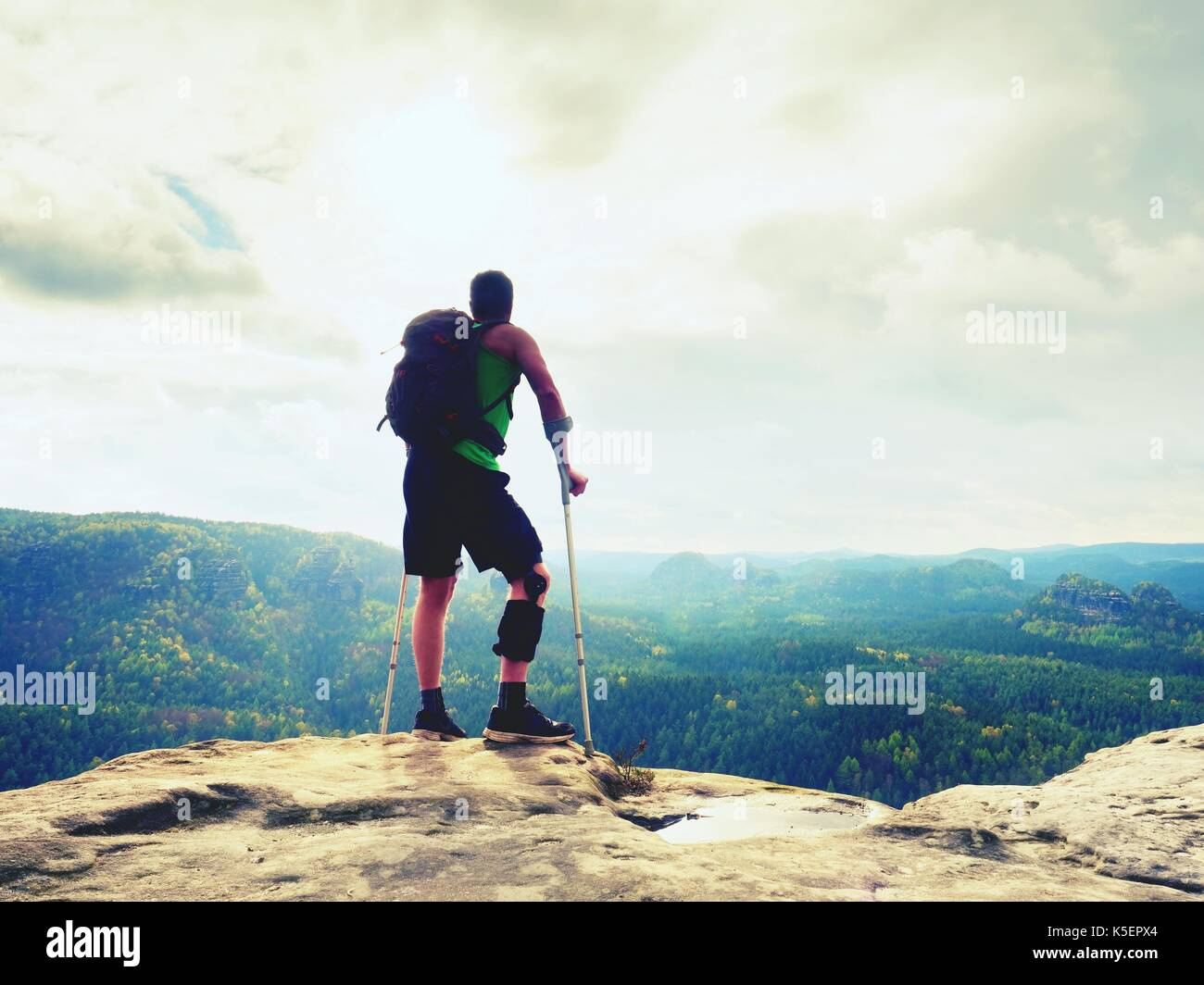 Man with a crutches in nature. Tourist with broken leg on crutches. Traveler with hurt leg in bandages stay on rocky  view point. Full length of man w - Stock Image