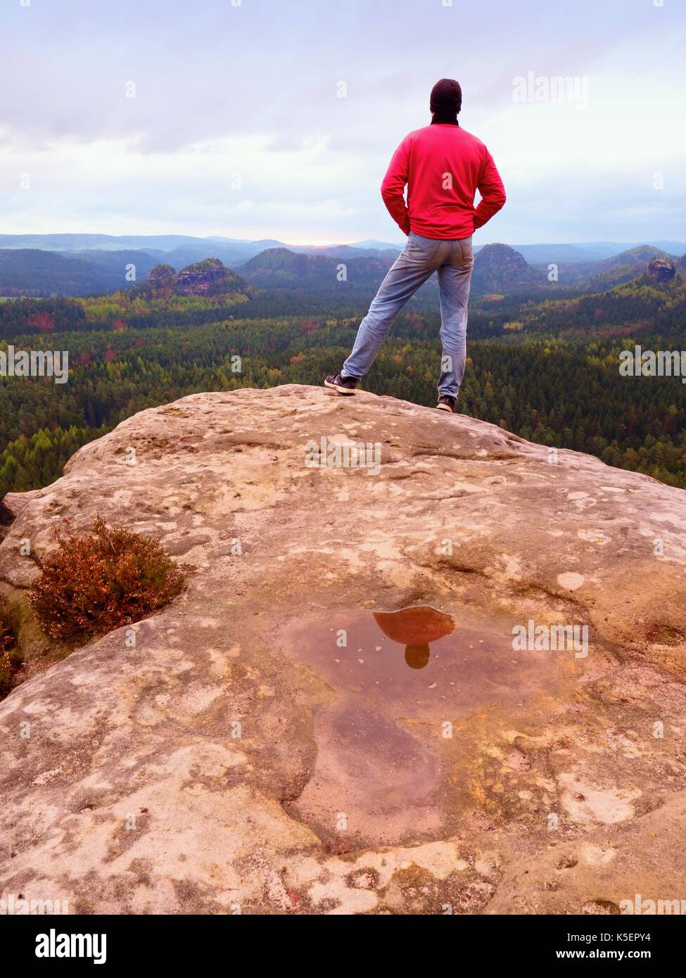 Hiker man stays on a rocky ridge and enjoy view over long valley to horizon. Cold Sun hidden in clouds. National Stock Photo