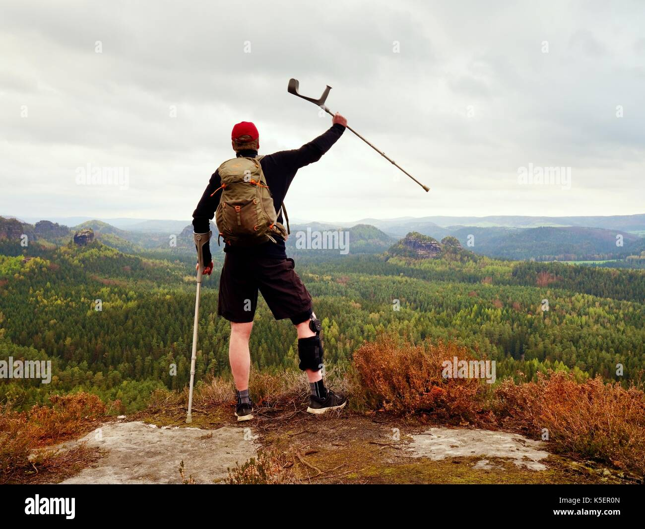 Hiker with broken leg in immobilizer. Tourist with medicine crutch above head achieved mountain peak. Deep misty valley bellow silhouette of happy man - Stock Image