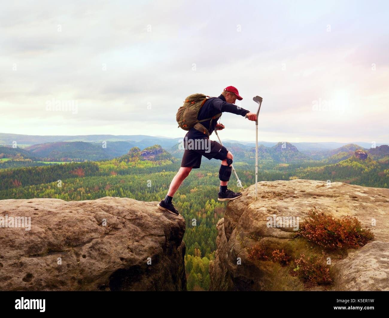 Tourist with medicine crutch above head achieved mountain peak. Hiker with broken leg in immobilizer. Deep misty valley bellow silhouette of happy man - Stock Image