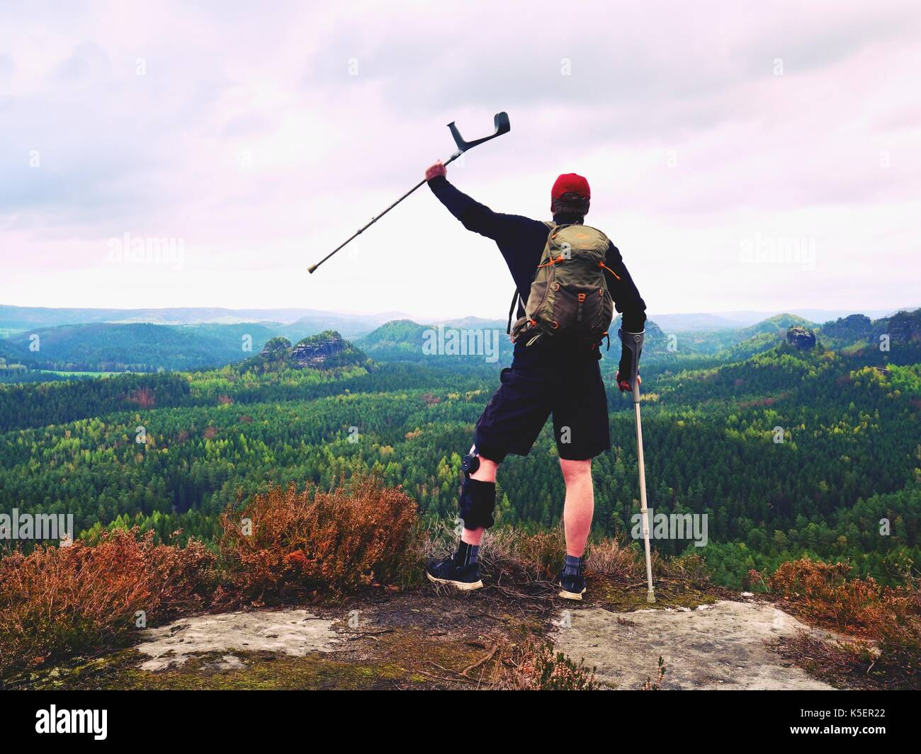 Man hiker Wearing Supportive Leg Brace and against the crutches. Natural forest park in background - Stock Image