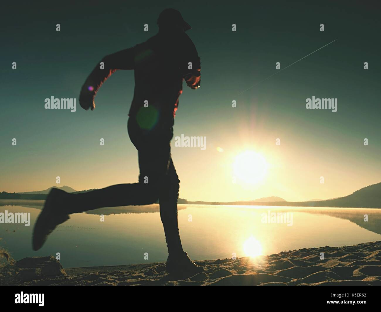 Running man. Boy quickly running on the morning beach. Sportsman runner, jogging guy during the sunrise above sandy beach - Stock Image