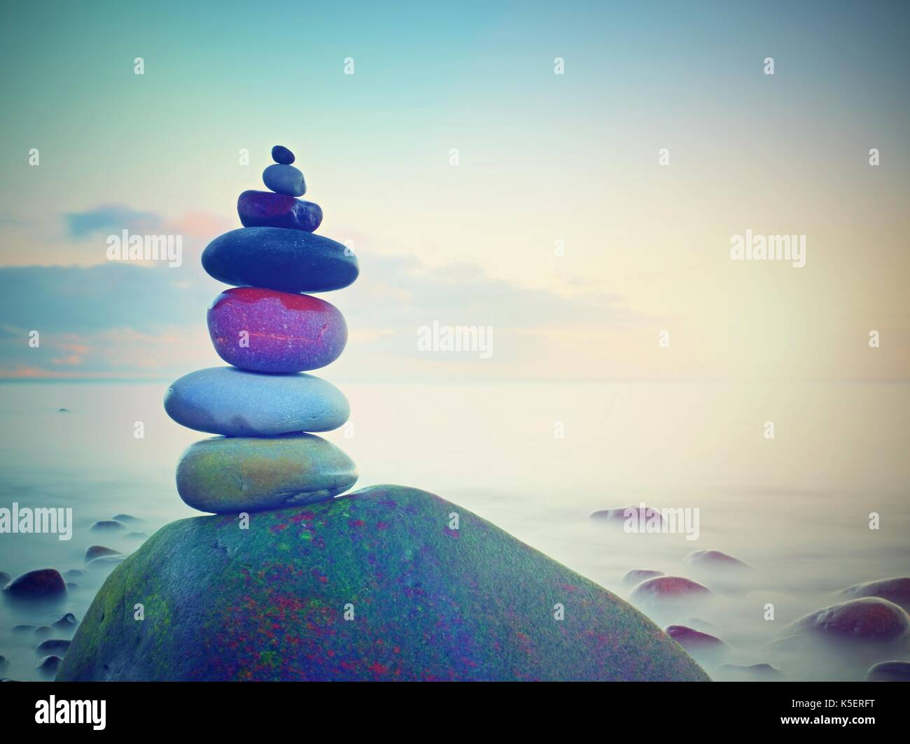 Balance of pebbles against the background of blurred sea.  Smooth atmosphere on hotel beach - Stock Image