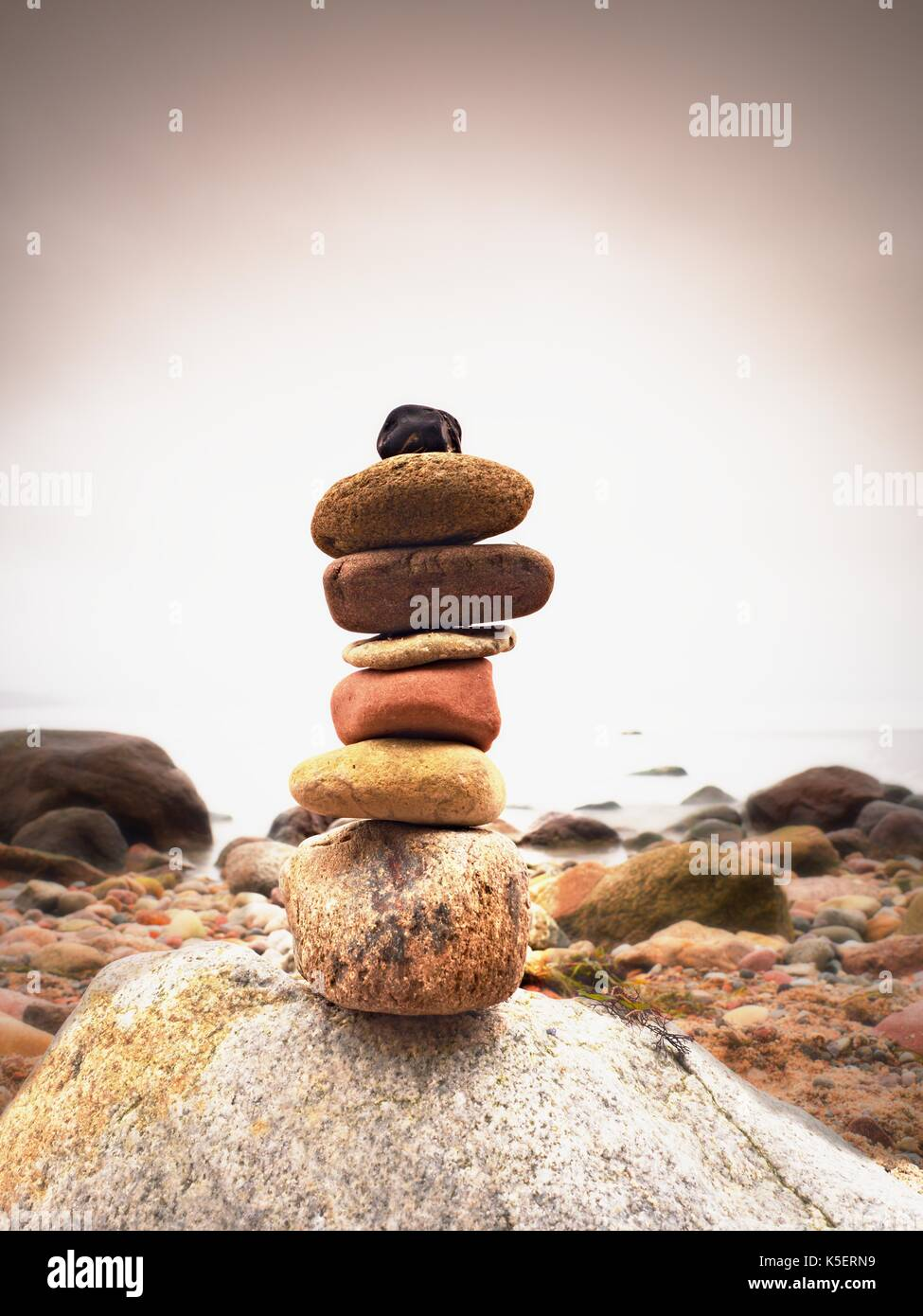 Stones pyramid symbolizing zen, harmony, balance pebbles. Ocean in background. Colorful flat stones for meditation lying on stony  sea  beach - Stock Image
