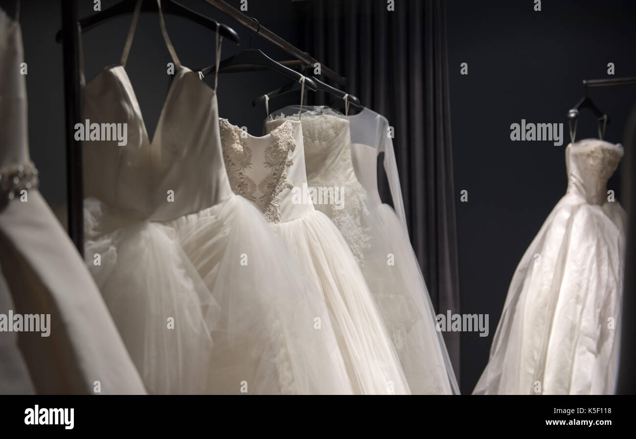 Selection of white wedding dresses or ball gowns on display hanging on rails with selective focus to one illuminated Stock Photo