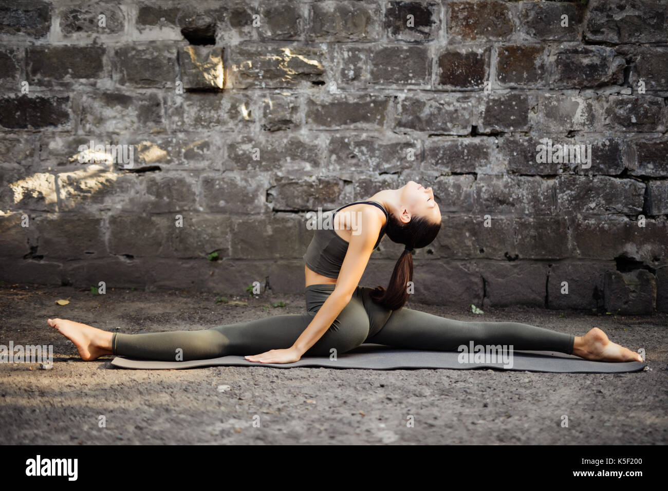 Beautiful young woman practicing yoga by a brick wall. - Stock Image